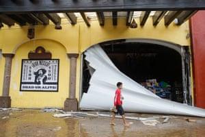 A boy walks by a damaged souvenir store in Los Cabos