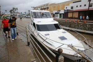 People walk past a yacht that was pushed on to San Lucas' main street in Los Cabos