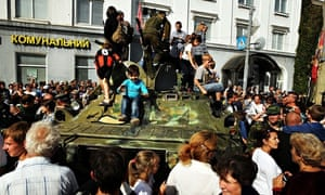 Children play on a separatist military vehicle in Lugansk as residents welcome back fighters