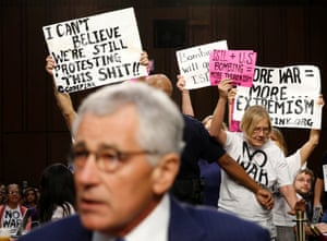 Anti-war protesters hold up signs as U.S. Secretary of Defense Chuck Hagel takes his seat to testify at the Senate Armed Services Committee hearing on U.S. policy toward Iraq and Syria and the threat posed by the Islamic State  on Capitol Hill in Washington September 16, 2014.