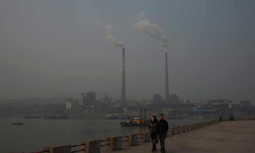A couple walk on the riverside as two chimneys emit smoke at a power plant across the river in China's Chongqing municipality.