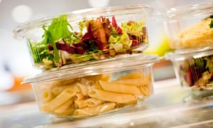 food packaging stacked on top of one another, containing salad and pasta