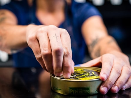 A member of staff opens a tin at Tincan