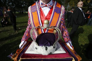 A crown is displayed by a colourful demonstrator.
