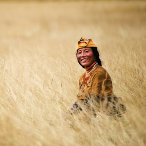 Kham region, Tibet. At the beginning of autumn, on a remote, high-altitude Tibetan plateau near Serxu, a Tibetan woman cuts hay to stock up for the long winter