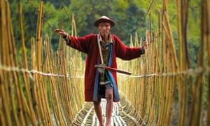 Arunachal Pradesh, India  An elderly Adi man walks tentatively across an ageing bamboo bridge. Adi, meaning 'hill man', are divided into Bogum and Onai