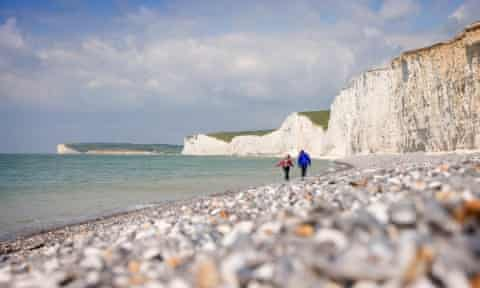 A couple walking along the pebble foreshore at Birling Gap, East Sussex
