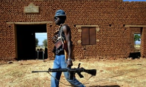 A Sudan Liberation Army rebel passes an abandoned building in the desert west of El Fasher, the capital of North Darfur state, in 2004.
