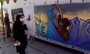 Shamsia Hassani with spray can outside the French Cultural Centre, Kabul.