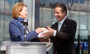 Mary Wilson, wife of the late Buffalo Bills owner Ralph Wilson, hands a football to New York Gov. Andrew Cuomo during a recent ribbon-cutting ceremony for renovations to Ralph Wilson Stadium.
