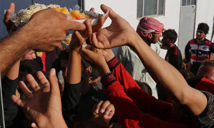 Displaced Iraqis from the Yazidi community gather for food at the Nowruz camp in Derike, Syria.