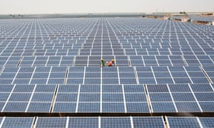 Workers install photovoltaic solar panels at the Gujarat solar park.