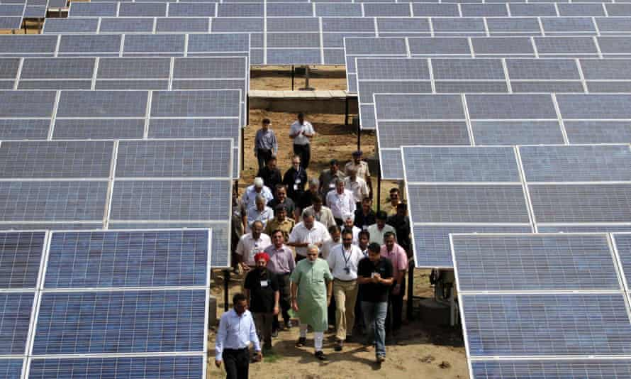 Gujarat Chief Minister Narendra Modi, center, walks among solar panels before inaugurating the 5 MW solar photovoltaic power plant at Khadoda, in Sabarkantha district, about 90 kilometers (56 miles) from Ahmadabad, India, Friday, June 10, 2011.