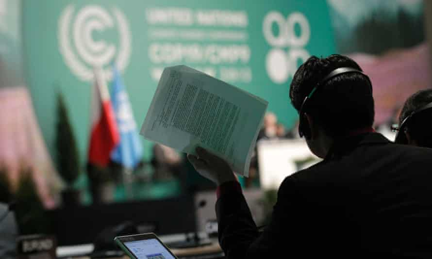 A man holds documents as he listens to statements of delegates during climate talks in Warsaw, Poland, in 2013