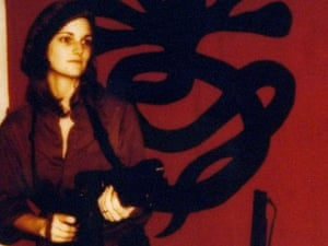 """Patricia """"Patty"""" Hearst, as """"Tania"""" in front of a poster issued by the Symbionese Liberation Army."""