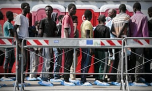 Disembarking immigrants wait to be processed by authorities in Naples after arriving aboard the tanker Virginio Fasan.