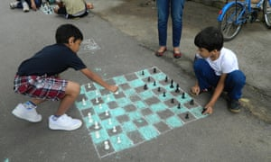 Children playing chess on a chalk chessboard on the street in Bangalore