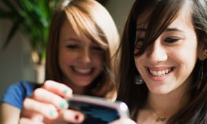 Two teenage girls using a smartphone.