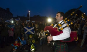 Yes campaigners are entertained by a piper outside the Scottish Parliament in Edinburgh.