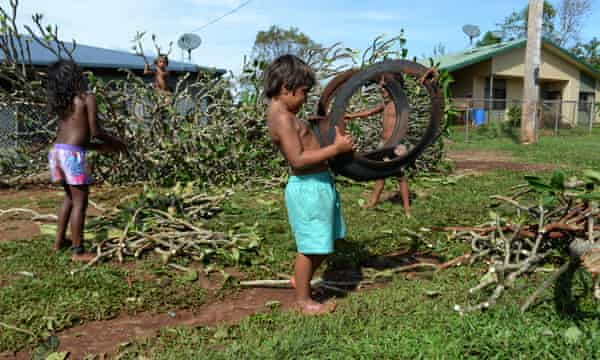Children in Hopevale, where many of the footballers are from, help with the clean up of debris in the town in the wake of Cyclone Ita .