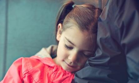 Girl resting on her dad's shoulder on train ride