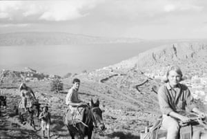 Marrianne ishtel riding donkey with Leonard Cohen behind her in Hydra, Greece October 1960