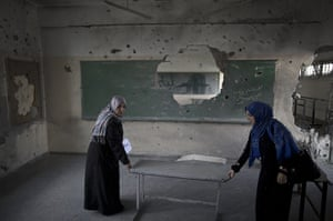 20 photos: Palestinian teachers carry a table in a classroom at a UN school in Gaza