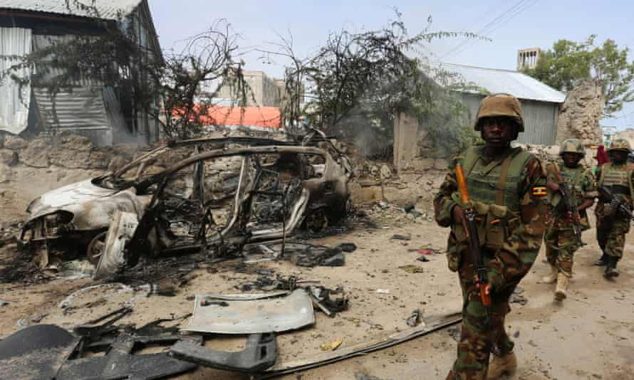Ugandan soldiers from the African Union Mission in Somalia (Amisom) patrol after the Mogadishu prison attack blamed on al-Shabaab militants.