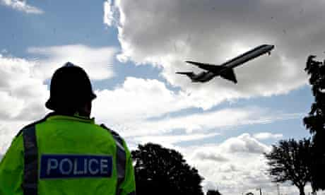 A police officer watches a plane land at Heathrow airport