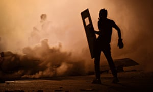 A Bahraini protester is surrounded by tear gas fired by riot police during clashes in July 2013