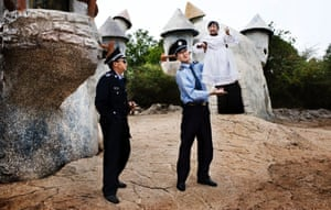 Two security guards hold up one of the park's workers. 'Perhaps the most dramatic, but not the most representative' of the images, says De Wilde