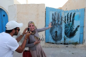 A Tunisian takes a photo of a mural by French artist Bom.K as part of the street art project 'Djerbahood'