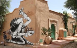 Brazilian artist Claudio Ethos works on his mural as part of the street art project 'Djerbahood'
