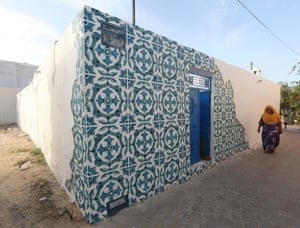 A Tunisian woman walks past a mural  by Portuguese artist Diogo Machado, better known as Add Fuel, as part of the street art project 'Djerbahood'