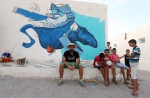Saudi Arabian artist Deyaa One  sit in front of the wall he is decorating as part of the street art project 'Djerbahood'