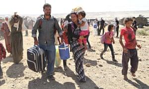 Syrians approach the Turkish border after fleeing Isis attacks on 60 Kurdish villages