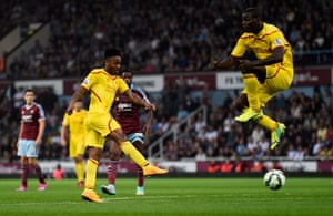 Mario Balotelli jumps to avoid the ball as Raheem Sterling scores.