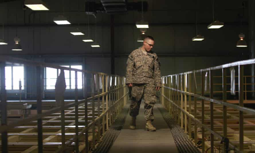 A US military guard watches over detainee cells inside the Parwan detention facility near Bagram Air Field.