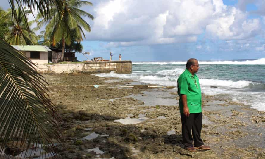 Marshall Islands president Christopher Loeak in front of his home. Loeak raised the height of a seawall around his home and concedes it is barely enough to protect his family from a 'climate emergency'.