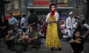 Uighurs wait at a bus stop
