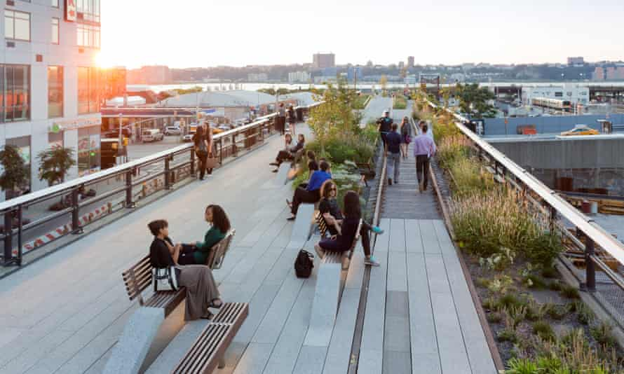"""Visitors to the High Line sit on """"conversation benches"""" as the sun sets over New York."""