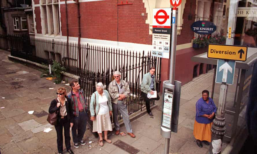 People wait at a bus stop in london