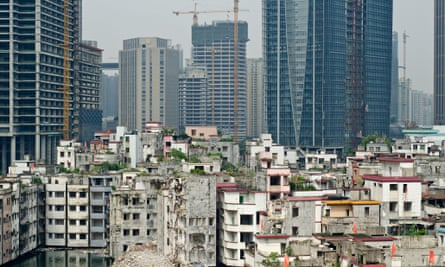 Xian village is dwarfed by high-rise buildings.