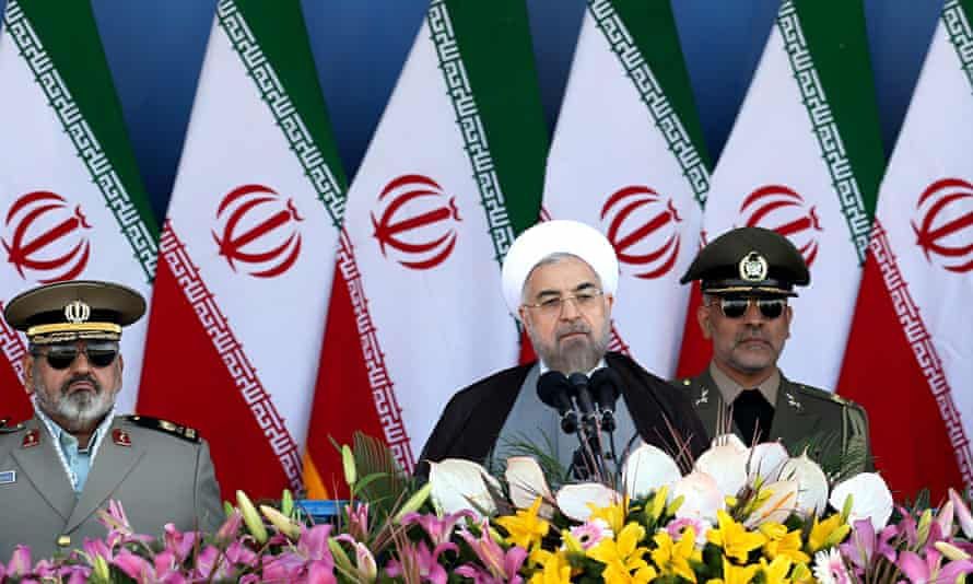 President Hassan Rouhani is hemmed in by Iran's military chiefs at a parade marking theIran-Iraq war