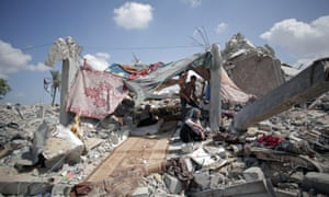 In this Saturday, Sept. 13, 2014 photo, a Palestinian family shelters amid the rubble of their destroyed house in the town of Khan Younis in the southern Gaza Strip.
