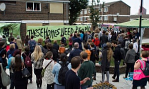People outside a boarded-up council house occupied by Focus E15