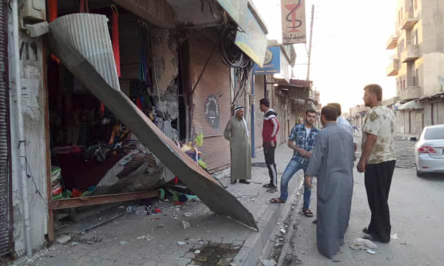 People inspect a shop damaged after what Islamist State militants say was a US drone in Raqqa.