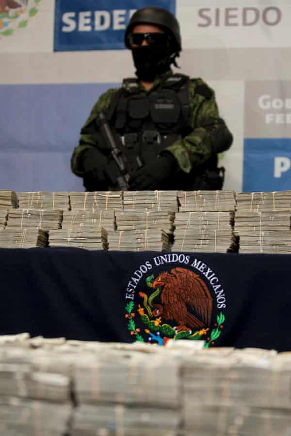 A Mexican soldier guarding $15m seized in an operation in Tijuana.