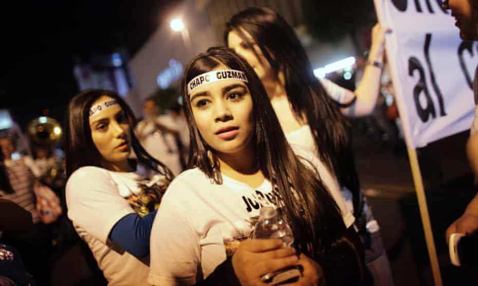 Young women wear headbands with Joaquín Guzmán's name, during a march to call for his freedom in his home state in the north-west of Mexico.
