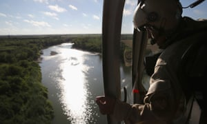 A helicopter crew member from the US Office of Air and Marine flies over the Rio Grande. The helicopters patrol day and night searching for drug and people smugglers.